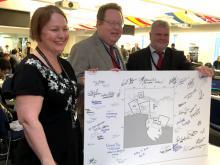 Jillian Dempster (Nouvelle-Zélande) et Evan Bloom (États-Unis) avec le président de la CCAMLR, Vasily Titushkin, montrant une carte de l'AMP de la mer de Ross signée par les délégués
