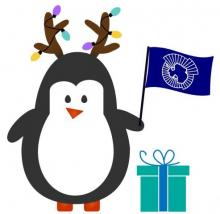 Penguin dressed as reindeer holding a CCAMLR flag